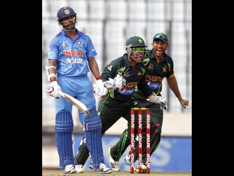 Shikhar Dhawan (L) reacts as Pakistan's wicketkeeper Umar Akmal (C) and Sohaib Maqsood celebrate his dismissal during their Asia Cup 2014 match in Mirpur. (Reuters Photo)