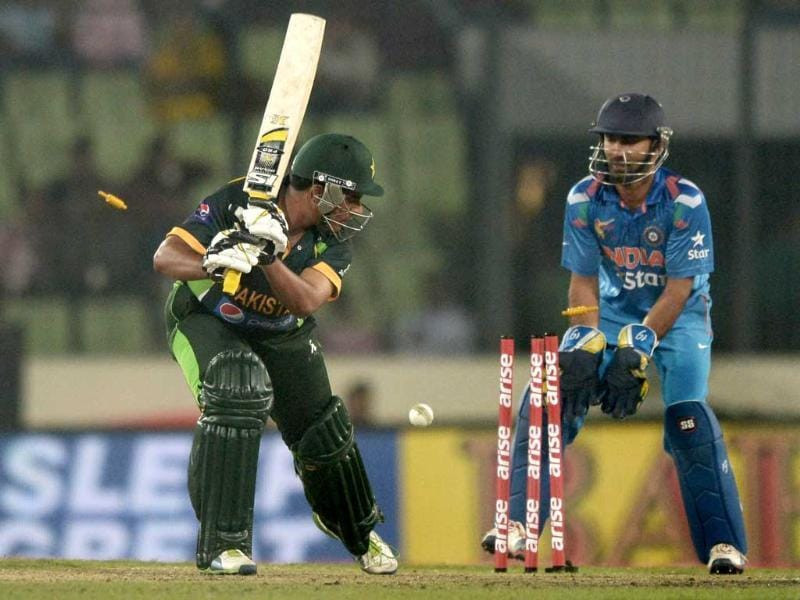 Pakistani batsman Sharjeel Khan is watched by Indian wicketkeeper Dinesh Karthik as he is clean bowled during the sixth match of the Asia Cup at the Sher-e-Bangla National Cricket Stadium in Mirpur. (AFP Photo)