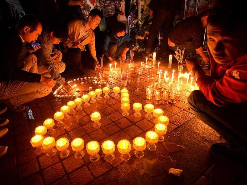 Chinese mourners light candles at the scene of the terror attack at the main train station in Kunming, Yunnan Province. (AFP Photo)