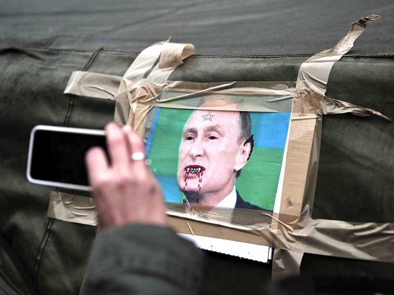 A woman clicks a picture with her mobile phone of a caricature of Russian President Vladimir Putin stuck onto a tent, within a rally to protest Russia's stance in the Ukraine crisis, on Kiev's Independence square. (AFP Photo)