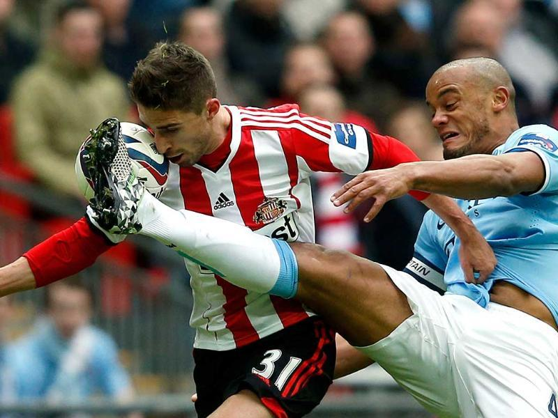 Sunderland striker Fabio Borini (L) manages to keep possession of the ball against a challenge from Manchester City defender Vincent Kompany (R) on his way to scoring the opening goal during the League Cup final football match at Wembley stadium. (AFP Photo)
