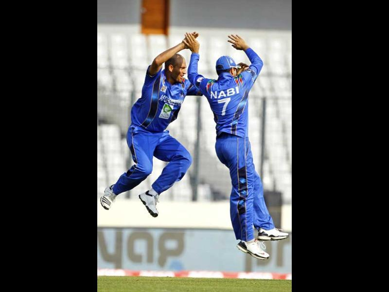 Afghanistan's Mirwais Ashraf (L) celebrate with teammates Mohammad Nabi (R) after taking the wicket of Sri Lanka's Mahela Jayawardene during their Asia Cup match in Mirpur. (AP Photo)