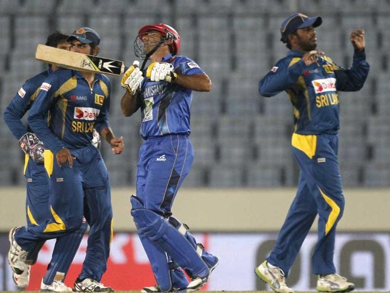 Afghanistan's Asghar Stanikzai (C) leaves the field as Sri Lanka's fielders celebrate his dismissal during their Asia Cup 2014 match in Mirpur. (Reuters Photo)