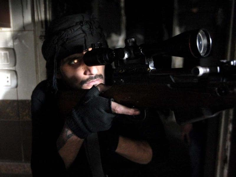 A rebel fighter takes aim at the location of pro-regime fighters, in the northern Syrian city of Aleppo. (AFP Photo)