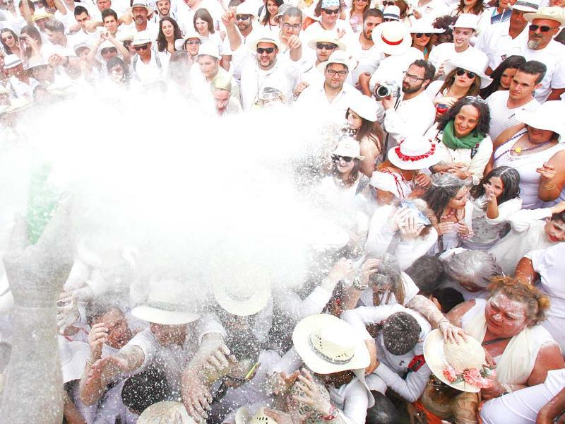 People throw talcum powder as they take part in the carnival of