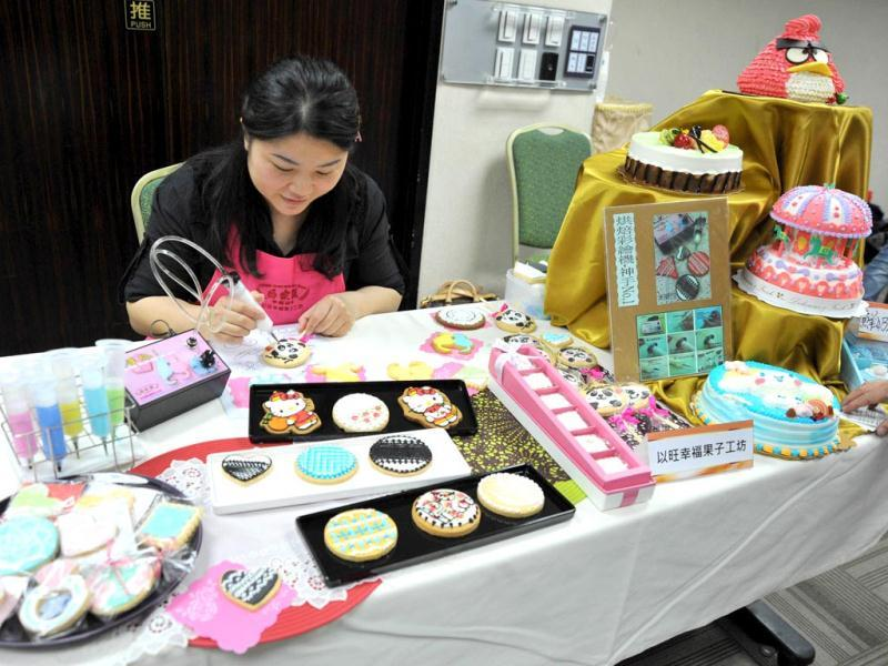 A cake maker uses a machine to draw a panda shape frosting on a cookies during a pre-show press conference for the Taipei International Bakery Show in Taipei. (AFP)