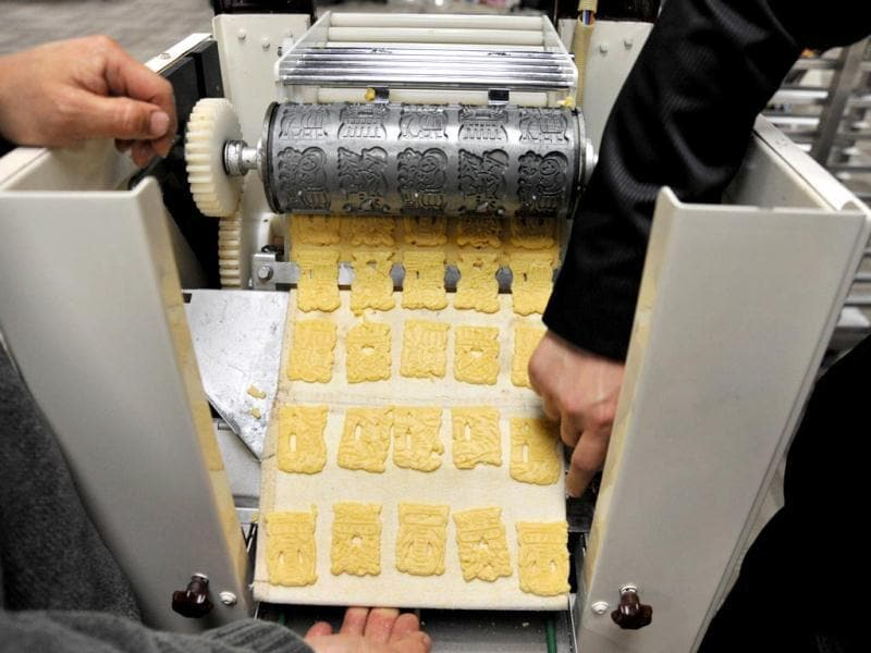 Two bakers make a cracker forming machine adjustment during the Taipei International Bakery Show, where thousands of bakery booths from many countries will be displayed. (AFP)