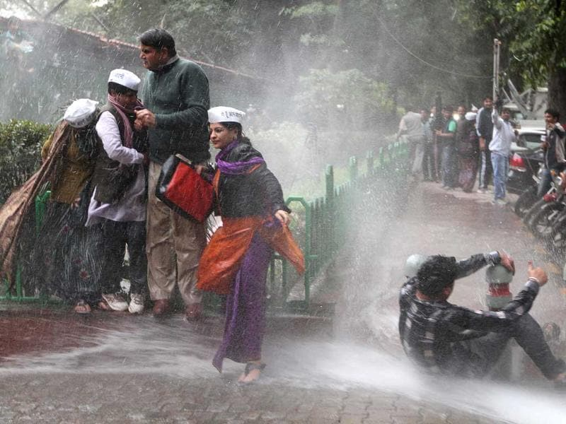 AAP leader Shazia Ilmi walking away as Delhi Police use water cannon on AAP workers during their protest outside BJP headquarters in New Delhi. (Arvind Yadav/ HT photo)
