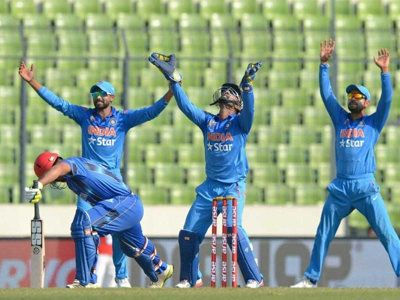 Dinesh Karthik, Virat Kohli and Ravindra Jadeja appeal for the dismissal of Afghan batsman Samiullah Shenwari during the ninth match of the Asia Cup at the Sher-e-Bangla National Cricket Stadium in Dhaka. (AFP Photo)