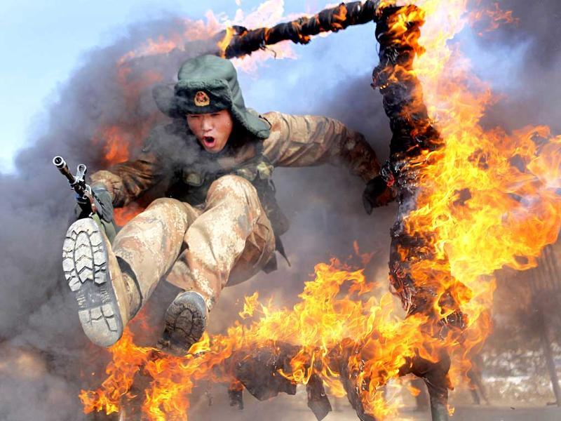 A Chinese frontier soldier from the People's Liberation Army jumps through a ring of fire as part of training in Heihe, Heilongjiang province. (Reuters Photo)