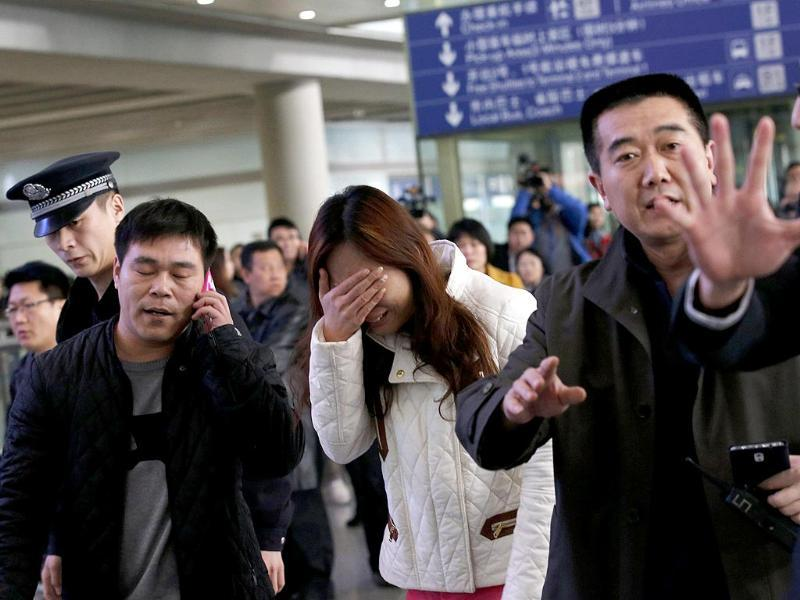 A woman (C), believed to be the relative of a passenger onboard Malaysia Airlines flight MH370, covers her face as she cries at the Beijing Capital International Airport in Beijing. (Reuters)