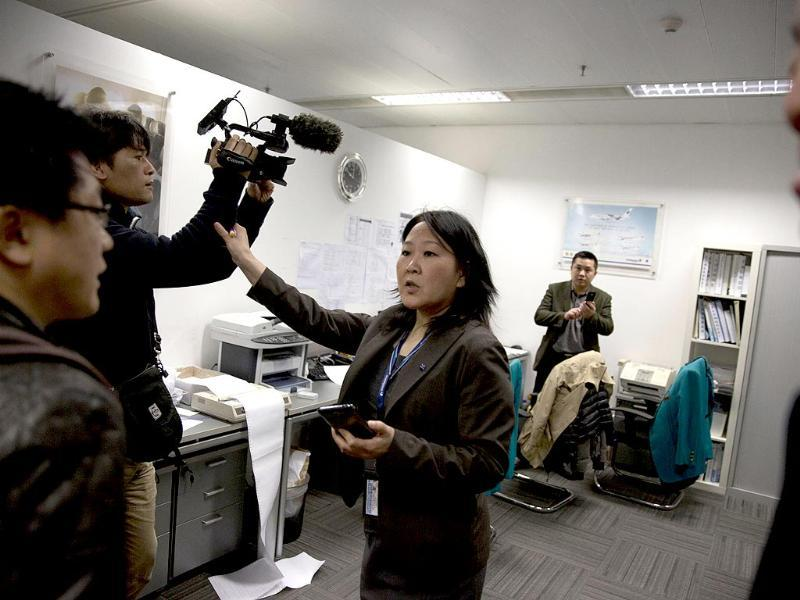 A staff member at the Malaysian Airlines' office in Beijing's International Airport reacts to journalists in Beijing, China. (AP Photo)