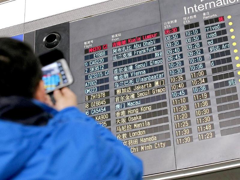 A man takes pictures of a flight information board displaying the Scheduled Time of Arrival (STA) of Malaysia Airlines flight MH370 (top, in red) at the Beijing Capital International Airport in Beijing (Reuters)