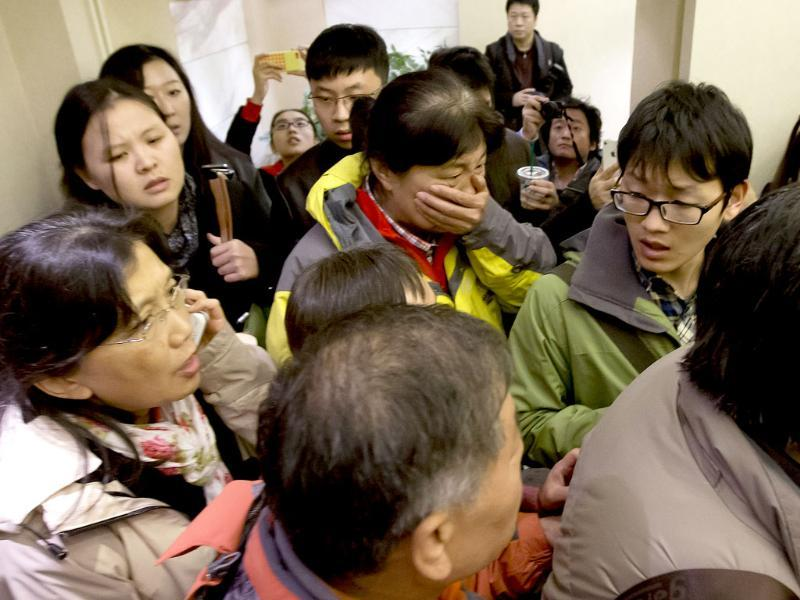 A woman, center, surrounded by media covers her mouth on her arrival at a hotel which is prepared for relatives or friends of passengers aboard a missing airline, in Beijing. (AP Photo)