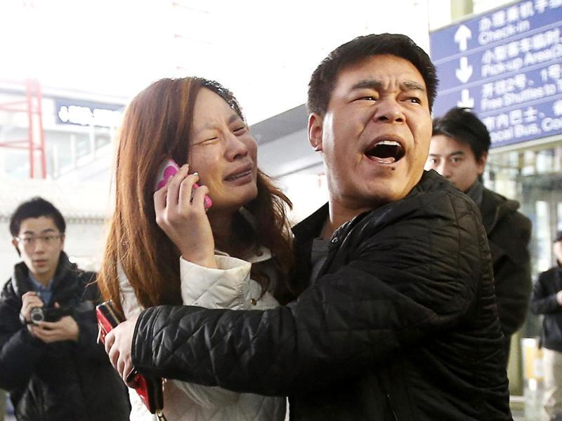 A relative of a passenger onboard Malaysia Airlines flight MH370 cries as she talks on her mobile phone at the Beijing Capital International Airport. (Reuters photo)