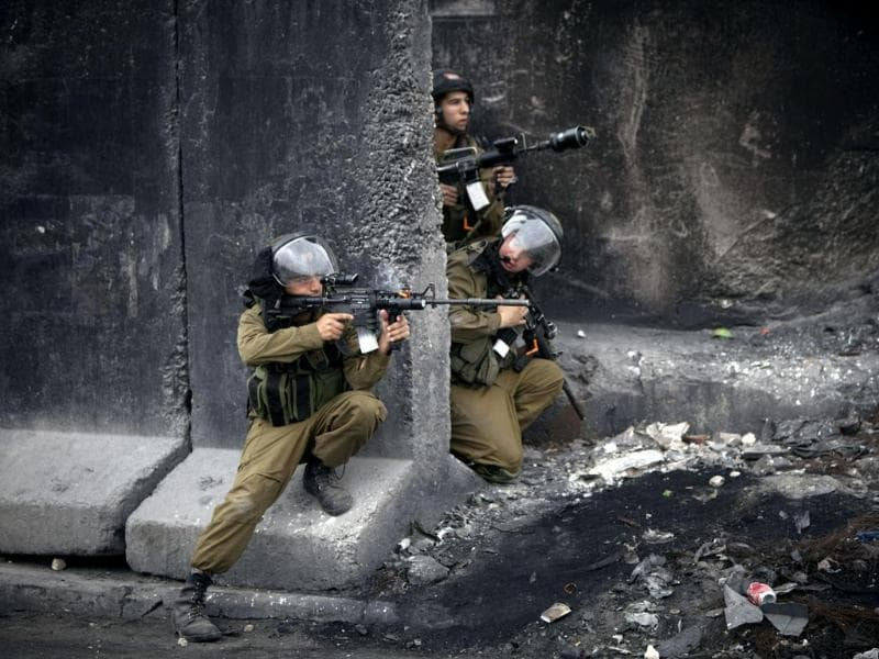 Israeli soldiers take positions during clashes following a march to commemorate International Women's Day at Qalandia checkpoint between Jerusalem and the West Bank city of Ramallah. (AP photo)