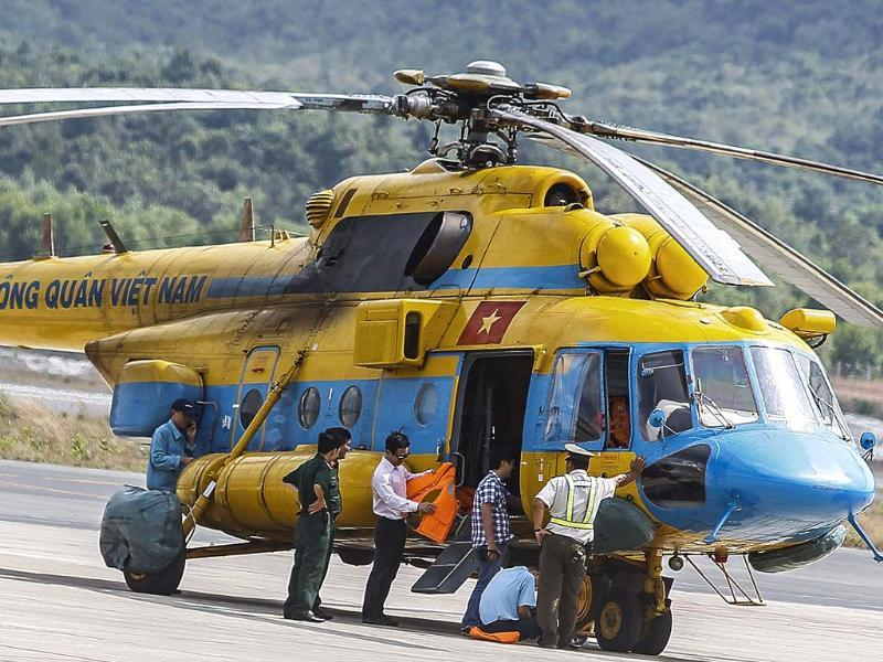 Vietnamese military personnel prepare a helicopter for a search and rescue mission for the missing Malaysia Airlines flight MH370 off Vietnam's southern coastline, at a military base on the southern island of Phu Quoc. (AFP photo)