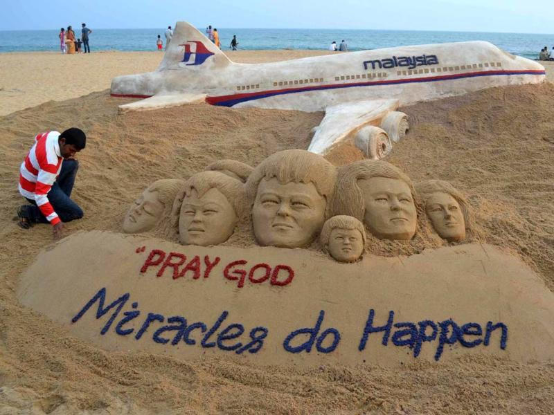 Sand artist Sudarshan Patnaik creates sand art sculpture wishing for the well being of the passengers of Malaysian Airlines flight MH370, on a beach in Puri. (Reuters photo)