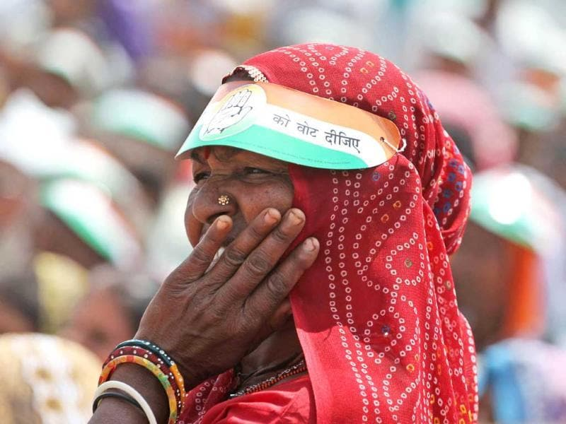 An woman listens to a speech by the country's ruling Congress party vice president Rahul Gandhi during an election rally at Balasinor, Gujarat. (AP Photo)