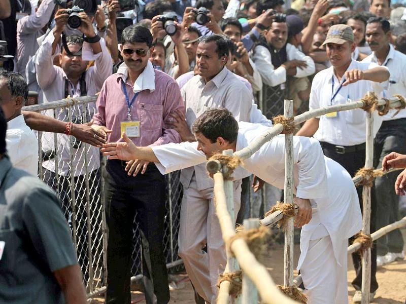 Congress party vice-president Rahul Gandhi, right, stretches out to greet a supporter during an election rally at Balasinor, Gujarat. (AP Photo)