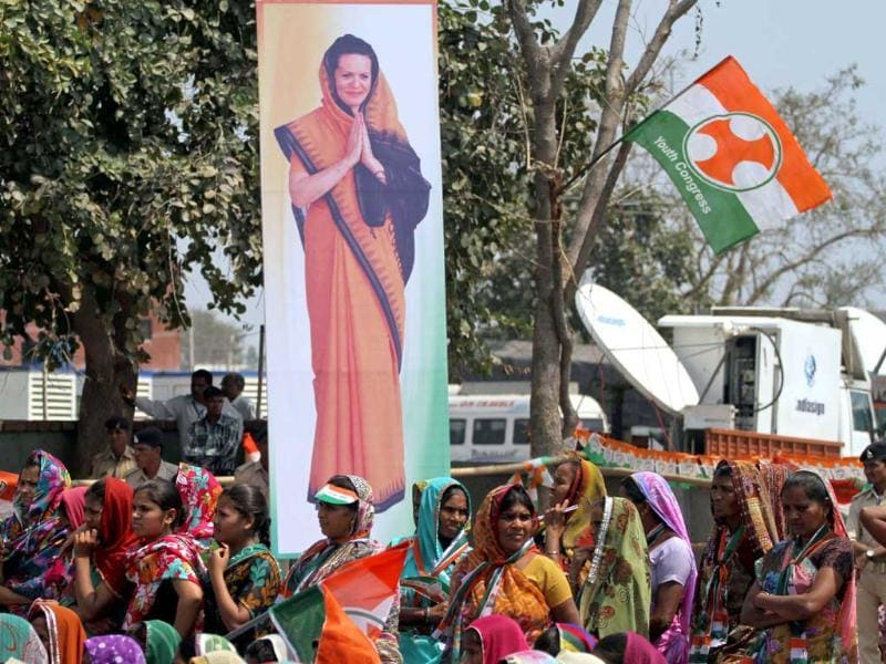 Women stand beside a poster of Congress party president Sonia Gandhi and listen to a speech by party vice-president Rahul Gandhi during an election rally at Balasinor, Gujarat. (AP Photo)