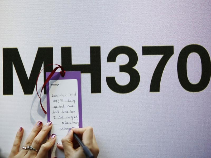 A tourist from Vietnam writes a message expressing hope for family members and those onboard the missing Malaysia Airlines flight MH370, in Kuala Lumpur. (Reuters Photo)