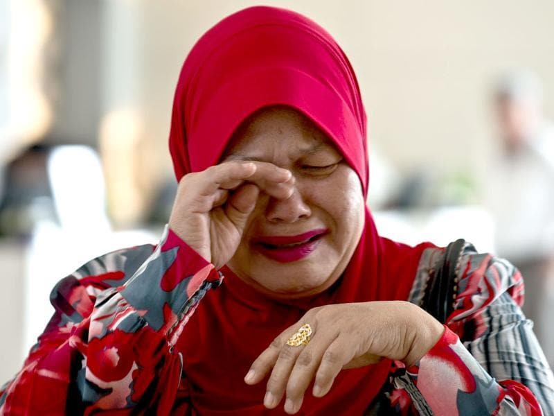 A relative of a passenger on board missing Malaysia Airlines (MAS) flight MH370 cries as she arrives at the Everly hotel in Putrajaya. (AFP Photo)