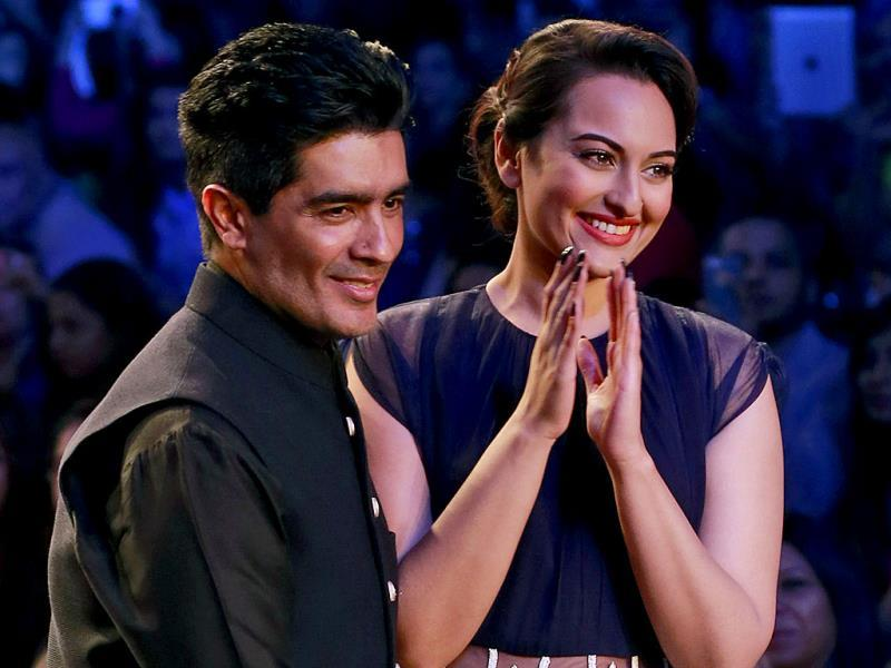 Sonakshi displays a creation by Indian designer Manish Malhotra, left, during the opening day of Lakme Fashion Week.(AP Photo)