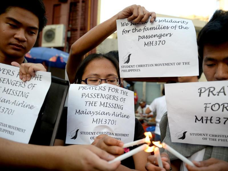 Students light candles as they hold placards in solidarity with families of the passengers of the missing Malaysia Airlines flight MH370 plane during a candle light vigil at the university belt in Manila. (AFP photo)