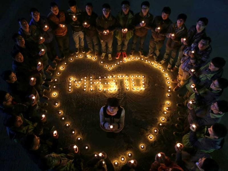 Construction site workers light candles to pray for passengers of the missing flight MH370, in Wuhan, Hubei province. (Reuters photo)