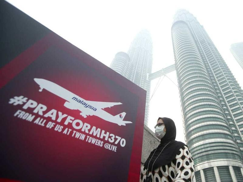 A woman wearing a mask against the haze walks past a board saying
