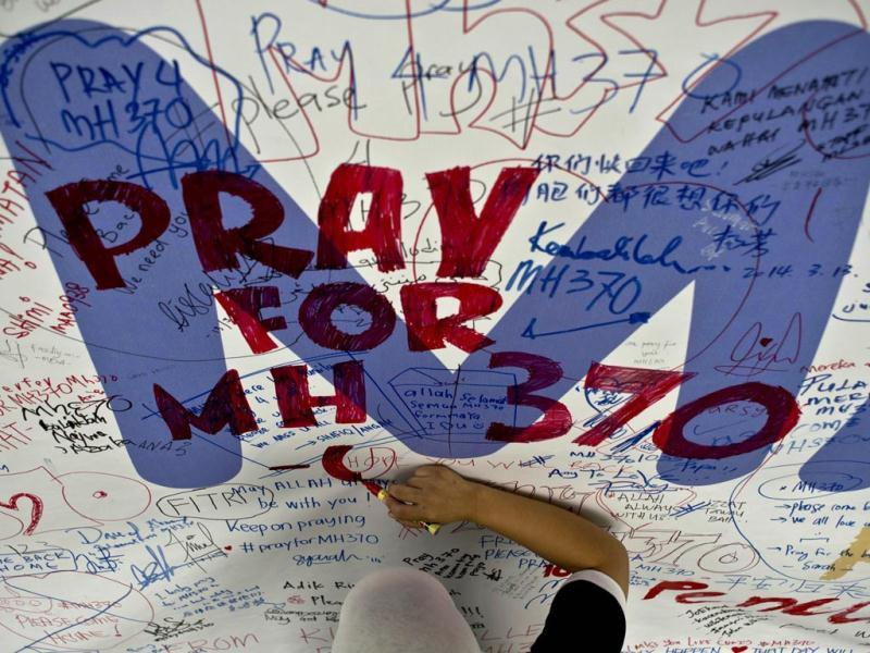 A Malaysia Airlines employee writes a message expressing prayers and well-wishes for passengers onboard the flight MH370 at the Kuala Lumpur International Airport. (AFP Photo)