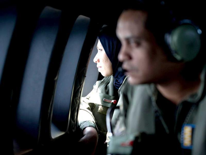 Crew members look outside windows from a Malaysian Air Force CN235 aircraft during a search and rescue operation to find the missing plane over the Strait of Malacca. (AFP Photo)