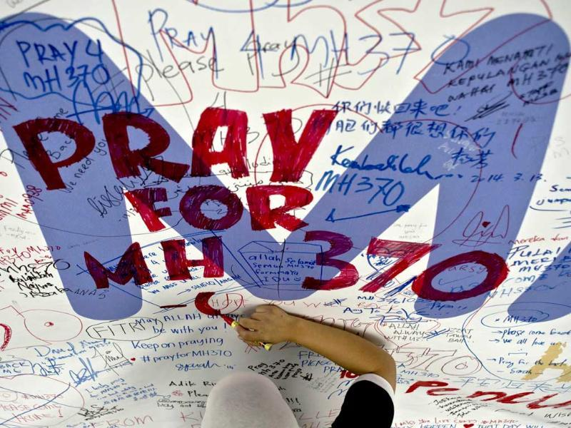 A Malaysia Airlines employee writes a message expressing prayers and well-wishes for passengers onboard missing Malaysia Airlines flight MH370 at Kuala Lumpur International Airport in Sepang. (AFP Photo)