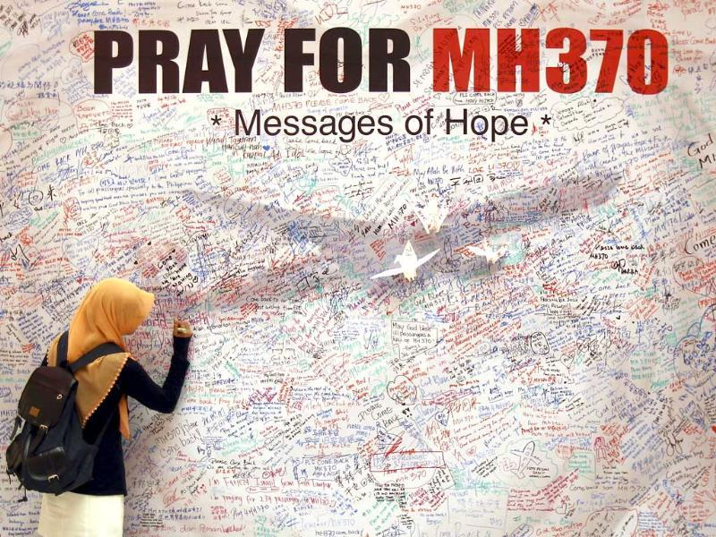 A woman writes a message for passengers aboard a missing Malaysia Airlines plane, at a shopping mall in Kuala Lumpur, Malaysia. (AP Photo)