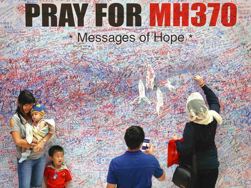 A woman leaves a messages of support and hope for the passengers of the missing Malaysia Airlines MH370 as others pose for picture in central Kuala Lumpur. (Reuters photo)