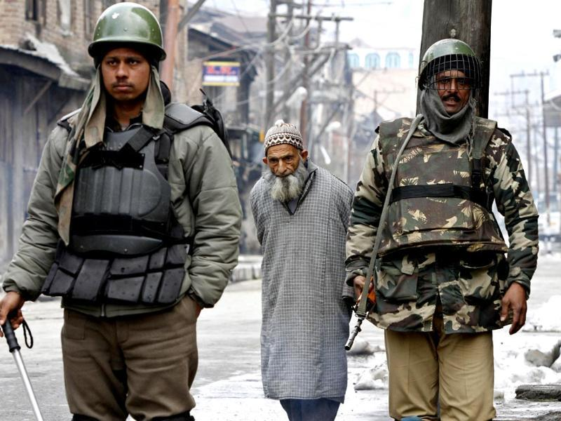 An elderly Kashmiri civilian walks as Indian paramilitary soldiers stand guard during restrictions in Srinagar. (AP photo)
