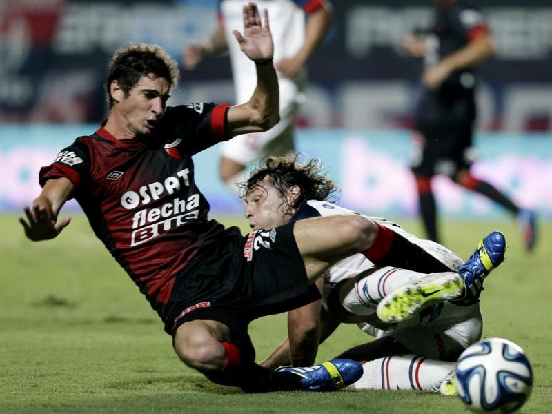 Colon de Santa Fe's Lucas Alario, left, and San Lorenzo's Fabricio Fontanini, collide in their battle for the ball during a national league match in Buenos Aires, Argentina. (AP photo)
