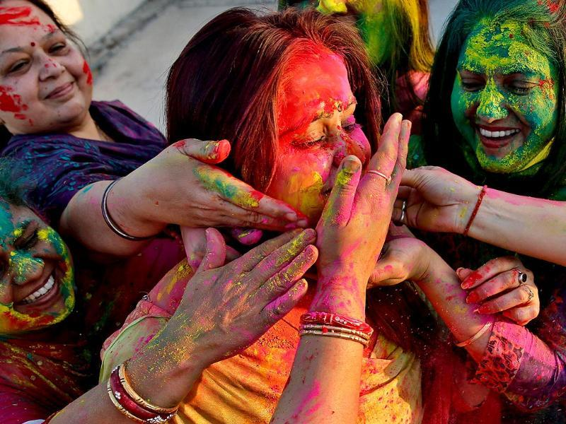 Revellers cover each other with coloured powder during celebrations for the Holi festival in Siliguri. (AFP photo)