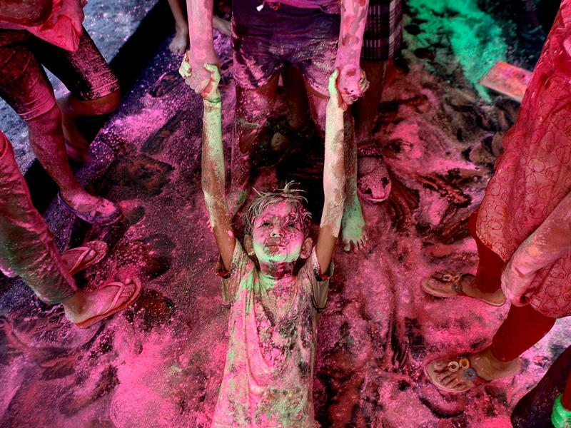 A boy drags another on the floor of an apartment as they play with colors during the Holi festival in Chennai. (AP Photo/Arun Sankar K)