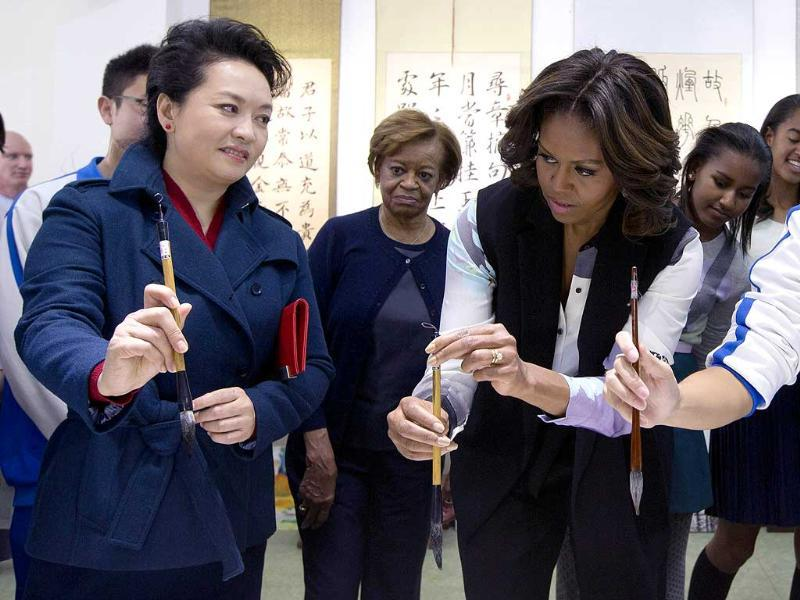 Peng Liyuan, wife of Chinese President Xi Jinping, shows US First Lady Michelle Obama how to hold a writing brush as they visit a Chinese traditional calligraphy class at the Beijing Normal School (AFP photo)