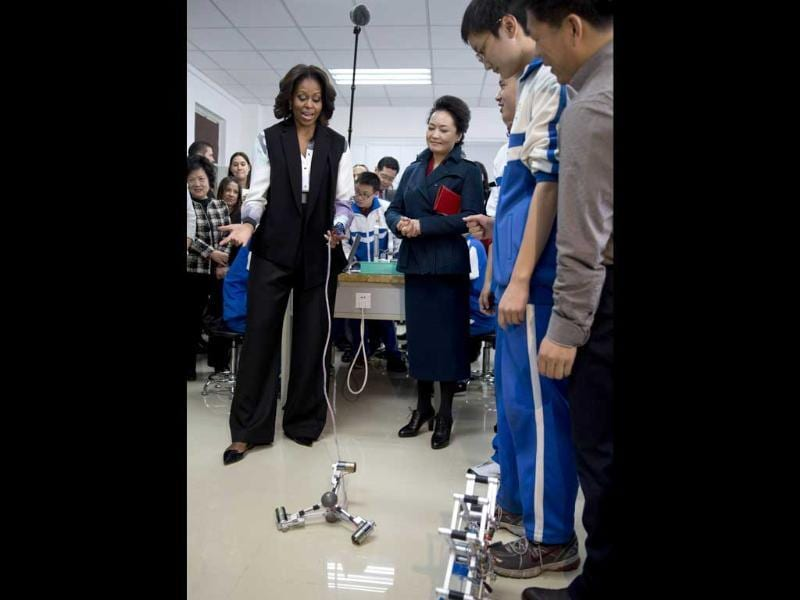 US First Lady Michelle Obama tries out a remote control mechanical robot next to Peng Liyuan, wife of Chinese President Xi Jinping as they visit the Beijing Normal School (AFP photo)