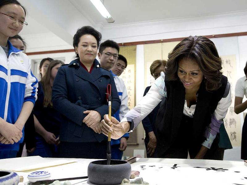 US First Lady Michelle Obama tries to write Chinese words with a brush as Peng Liyuan, wife of Chinese President Xi Jinping, looks on as they visit a Chinese traditional calligraphy class at the Beijing Normal School (Reuters photo)