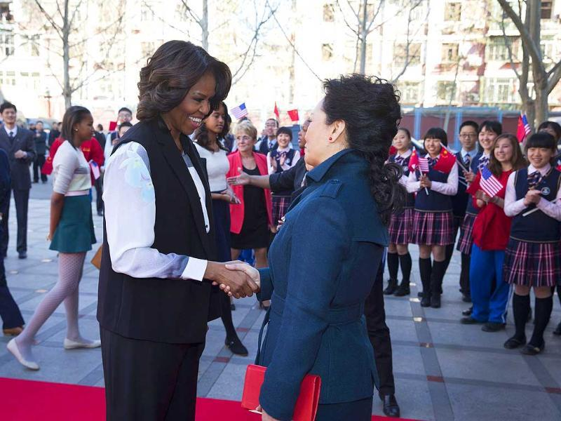US first lady Michelle Obama is greeted by Peng Liyuan, wife of Chinese President Xi Jinping, upon arrival for a visit to the Beijing Normal School, a school which prepares students for university abroad, in Beijing (Reuters photo)