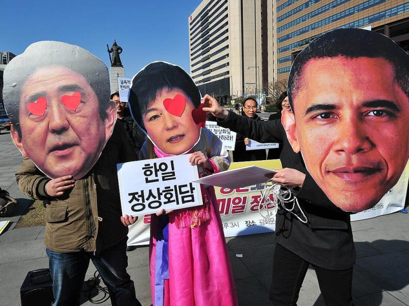 South Korean activists wearing the masks of South Korean President Park Geun-Hye (C) and Japanese Prime Minister Shinzo Abe (L) stand as another activist wearing the mask of US President Barack Obama (R) puts heart stickers over their eyes. (AFP Photo)