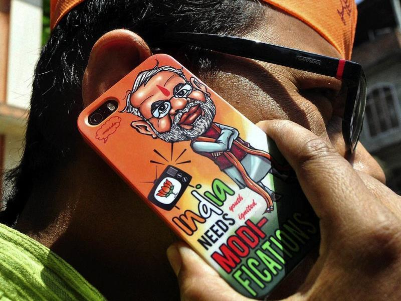 A BJP member using a mobile handset campaigns for BJP's prime ministerial candidate Narendra Modi in Guwahati. (PTI Photo)