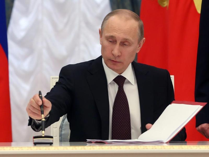 Russia's President Vladimir Putin signs a law on ratification of a treaty making Crimea part of Russia, during a ceremony in the Kremlin in Moscow. (AFP photo)