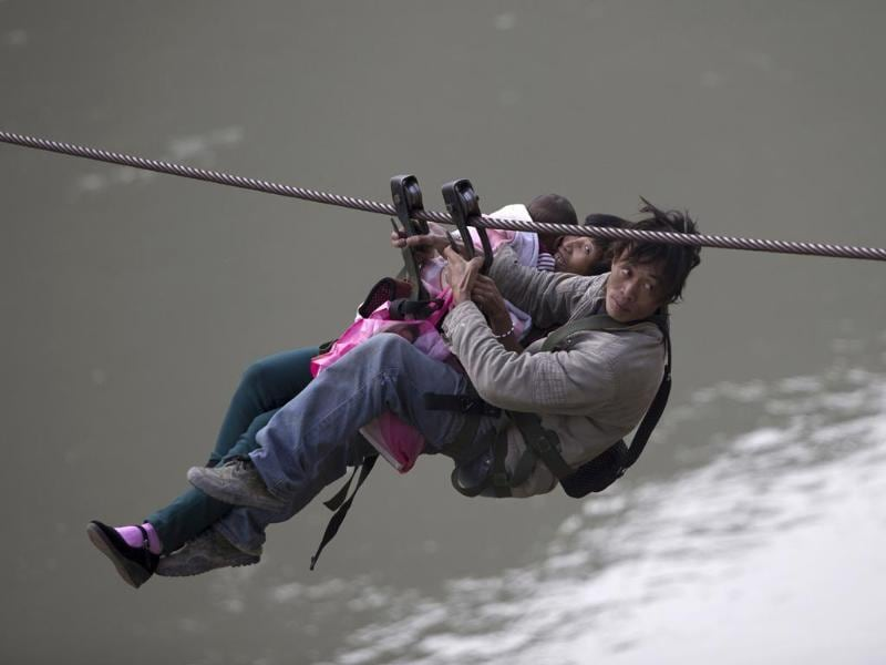 A man, his wife and their child use a zip-line to cross the Nujiang River in Lazimi village of Nujiang Lisu Autonomous Prefecture. Residents have been using the zip-line for years to cross the river as there is no bridge nearby, local media reported. (Reuters photo)