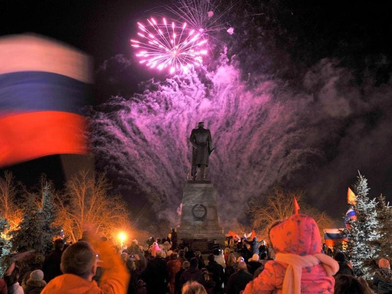 A man waves a Russian flag as people look at fire works in the center of the Crimean city of Sevastopol (AFP photo)