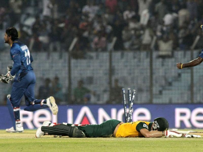 South Africa's David Miller lies on the ground after failing to reach the crease, as Sri Lankan cricketers celebrate during their ICC World Twenty20 match in Chittagong. (AP Photo)